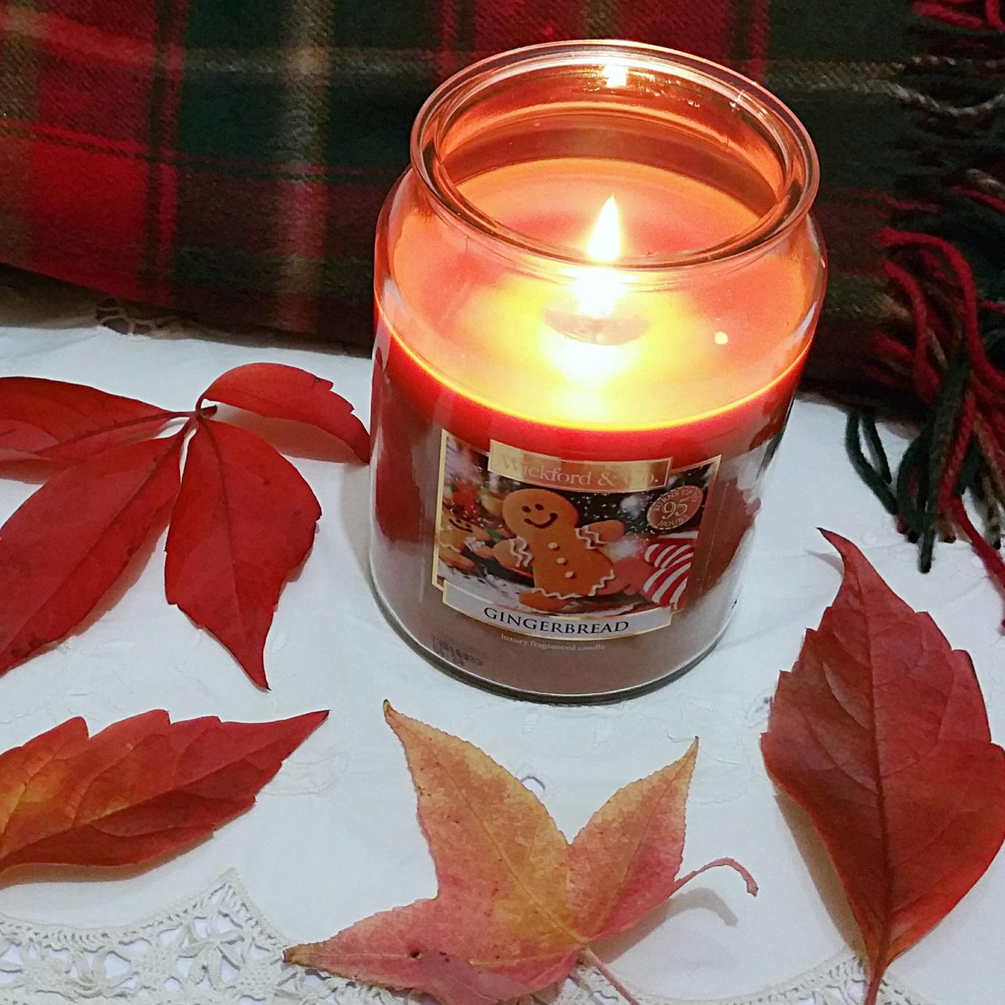 A lit candle surrounded by autumn leaves