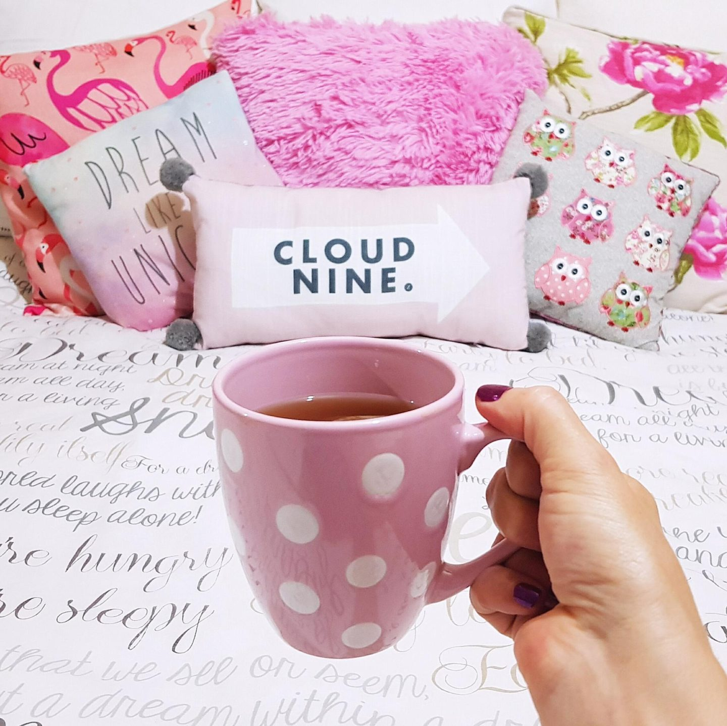 A mug of warm tea near a pile of fluffy cushions